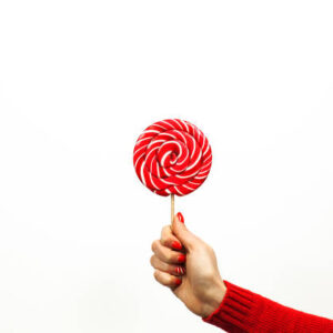 Red and white spiral lollipop in woman hand isolated on white background. Girls holding hard candy cane caramel on stick, sweets holidays concept, copy space for text